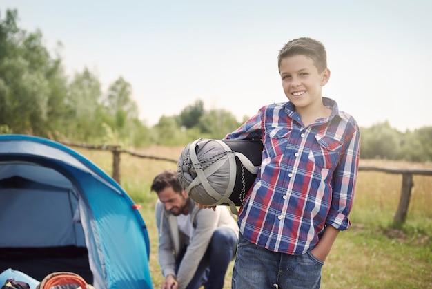 Père et fils plantant une tente