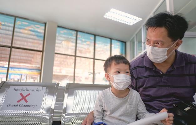 Père et fils portant un masque médical de protection dans la zone publique
