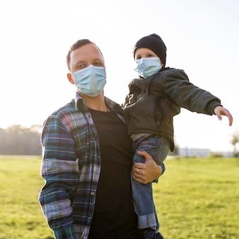 Père et fils portant des masques médicaux dans le parc