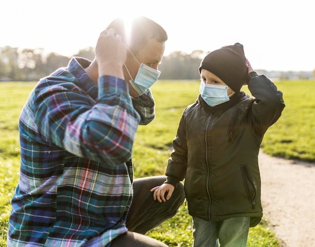 Père et fils portant des masques médicaux à l'extérieur