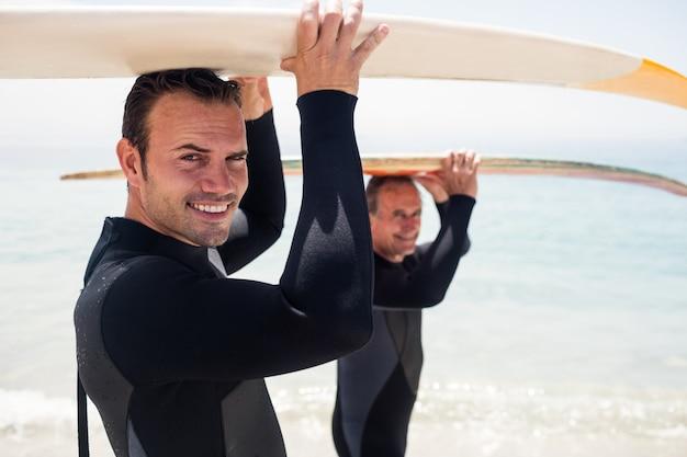 Père et fils portant une planche de surf sur la tête