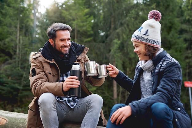Père et fils portant un toast dans la forêt