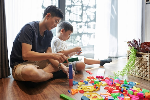Père et fils préadolescent assis par terre à la maison et construisant des tours avec des blocs en plastique