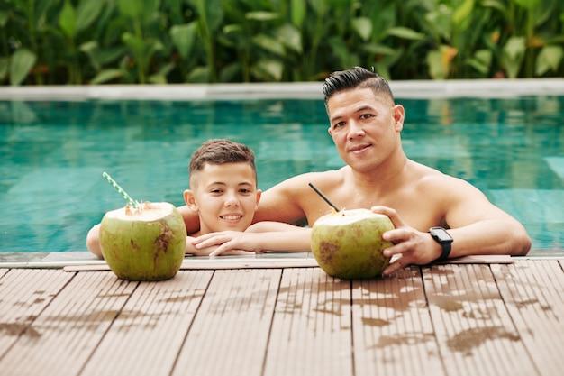 Père et fils préadolescent, passer du temps dans la piscine et déguster des cocktails rafraîchissants à la noix de coco