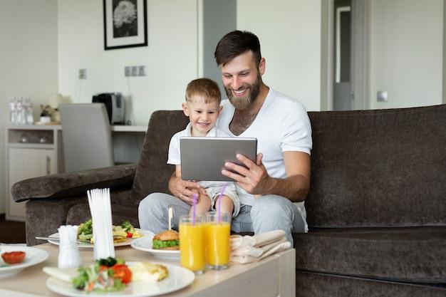 Le père et le fils prennent le petit déjeuner dans une chambre d'hôtel et regardent leur ordinateur portable.