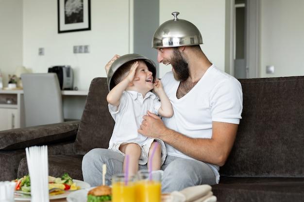 Père et fils prennent le petit déjeuner dans une chambre d'hôtel et se livrent, rient.