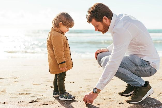 Père et fils ramassant un caillou