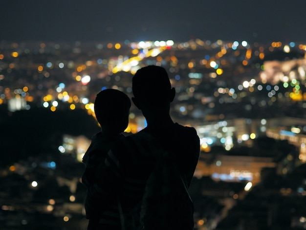 Père et fils en regardant la ville de nuit.