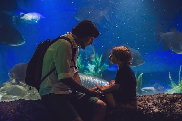 Père et fils regardent les poissons dans l'aquarium de l'océanarium