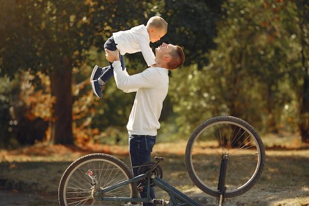 Père avec fils réparer le vélo dans un parc