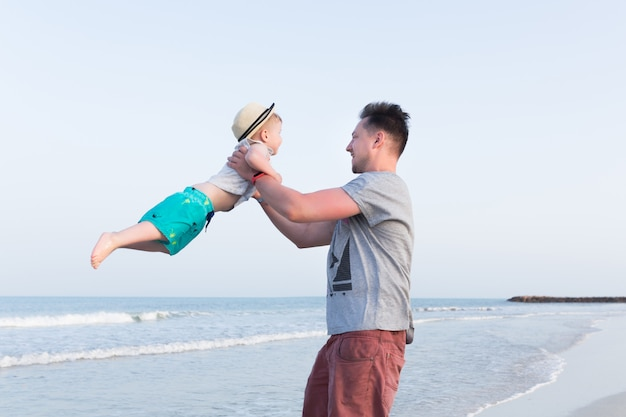 Père et fils s'amusant sur une plage