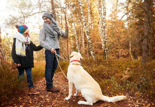 Père et fils s'entraînant avec un chien
