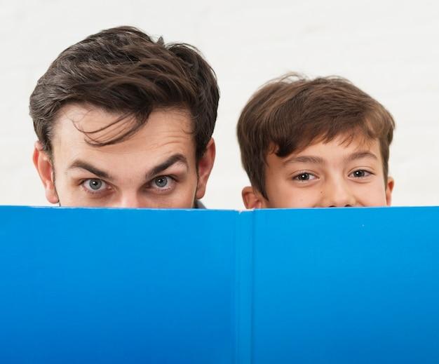 Père et fils se couvrant le visage avec un livre bleu
