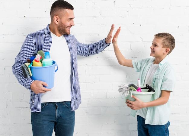 Le père et le fils se font plaisir tout en tenant des produits de nettoyage