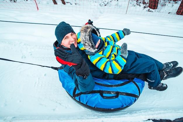 Père avec fils sur snow tube. tirez jusqu'à la colline. heure d'hiver