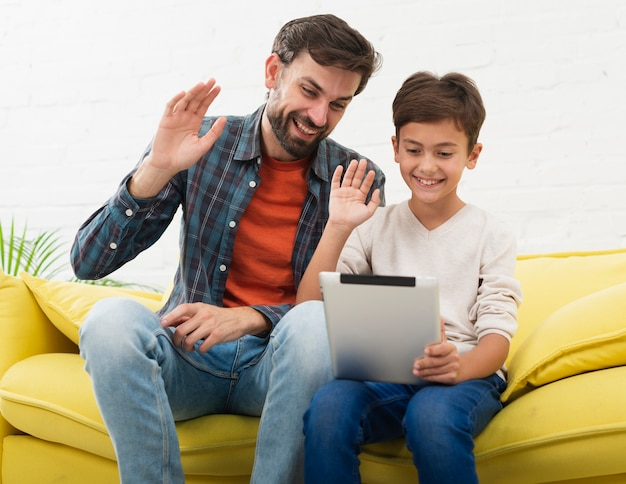 Père et fils tenant une tablette et saluant