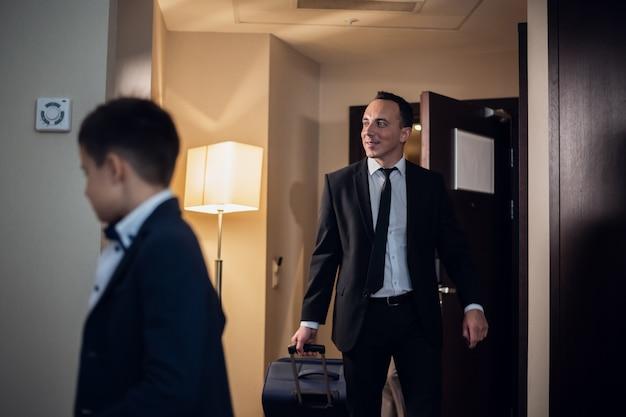 Père et fils en tenue de soirée entrant dans une chambre d'hôtel, le père porte une grande valise