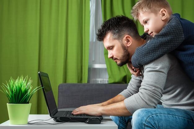 Père et fils travaillent sur un ordinateur portable.