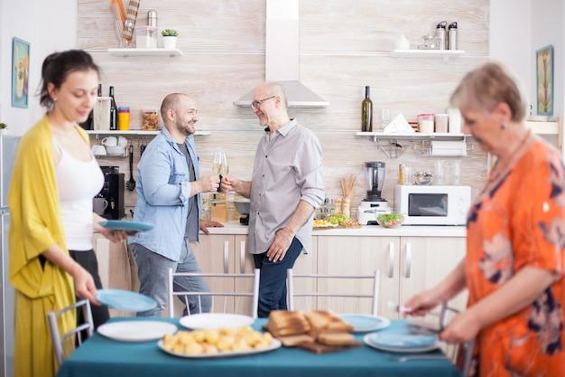 Père et fils trinquant avec du vin et souriant l'un à l'autre. mère et fille mettant des assiettes sur la table pour le déjeuner.