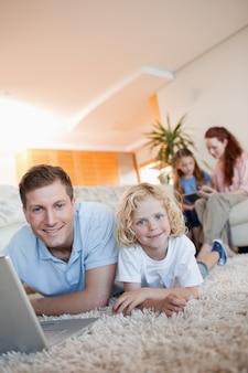 Père et fils utilisant internet sur le sol