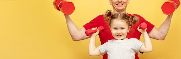 Père fort en tshort rouge et formation de fille mignonne avec des haltères isolés sur mur jaune
