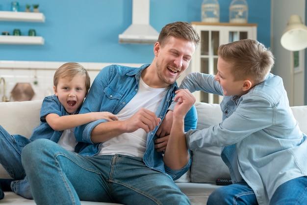 Père avec frères et sœurs jouant à l'intérieur