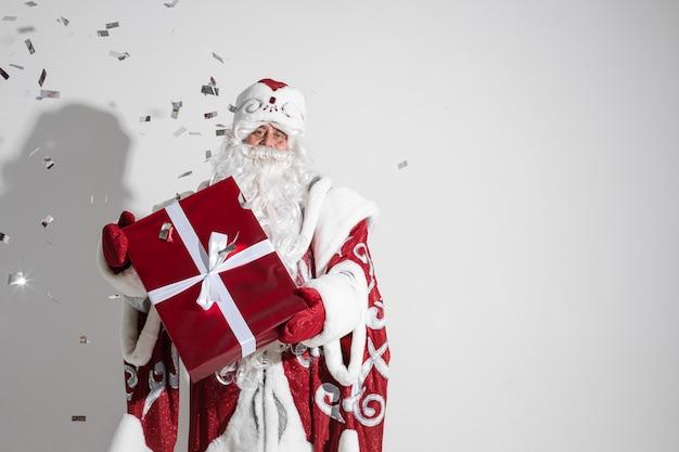 Père givre en long manteau chaud, mitaines rouges et un chapeau tient un cadeau de noël avec beaucoup de confettis autour de lui