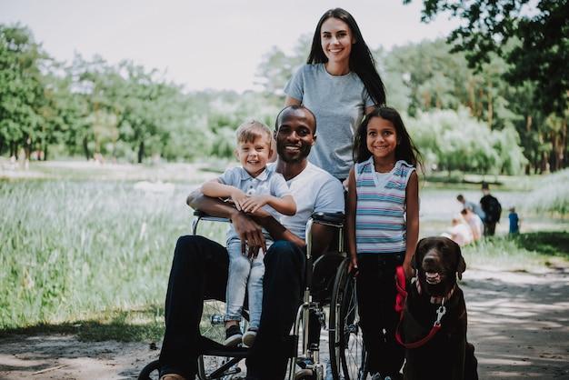 Père handicapé en fauteuil roulant tenant son fils dans un parc