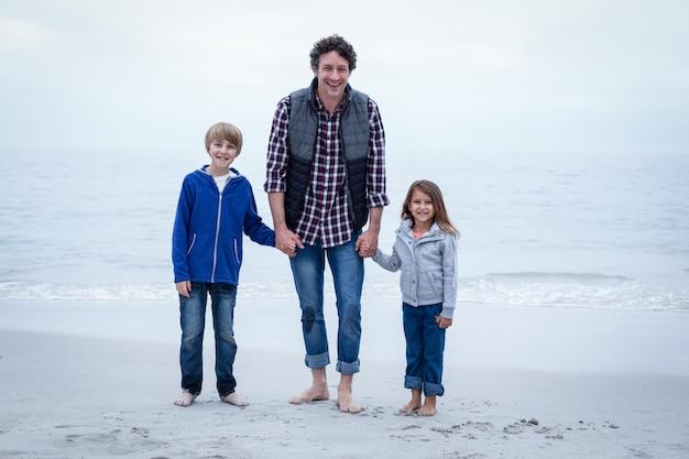 Père heureux avec des enfants au bord de la mer