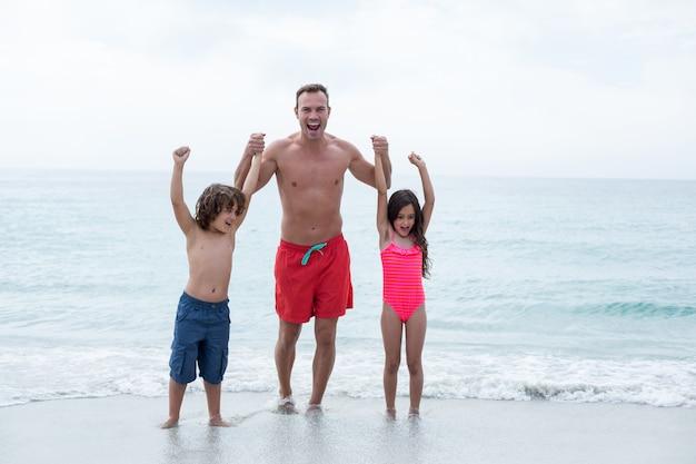 Père heureux avec des enfants profitant de la plage