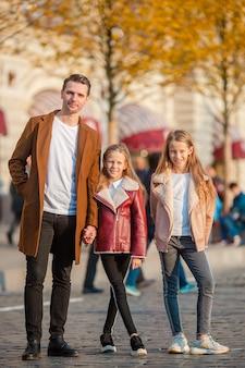 Père heureux et petites filles adorables à l'extérieur de la ville.