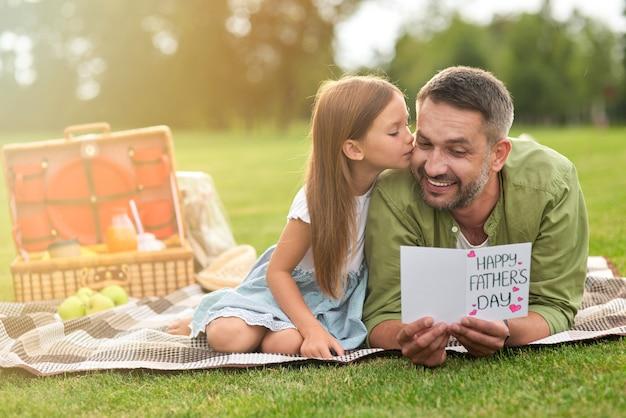 Un père heureux a reçu une carte postale faite à la main de sa fille petite fille et de son papa en train de pique-niquer