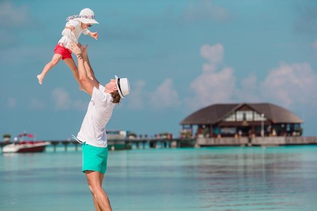 Père heureux et sa petite fille adorable à la plage tropicale s'amuser