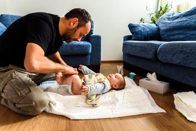 Un père impliqué dans le soin de ses enfants en changeant la couche sale de sa fille. notion de conciliation familiale travail