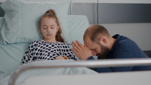 Père inquiet priant pour le rétablissement de la santé de sa fille malade après avoir subi une intervention chirurgicale à l'hôpital. petit enfant avec tube nasal d'oxygène dormant pendant l'examen de maladie