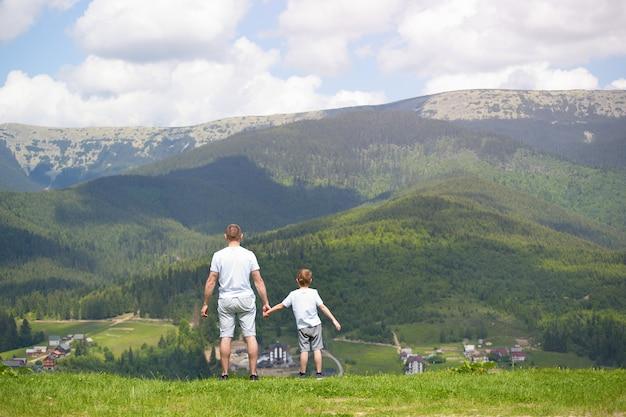 Père et jeune fils debout sur la pelouse et admirant les montagnes.