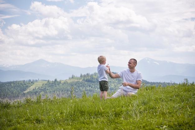 Père et jeune fils soufflent des pissenlits assis dans l'herbe sur une forêt verdoyante, les montagnes et le ciel avec des nuages. relation amicale