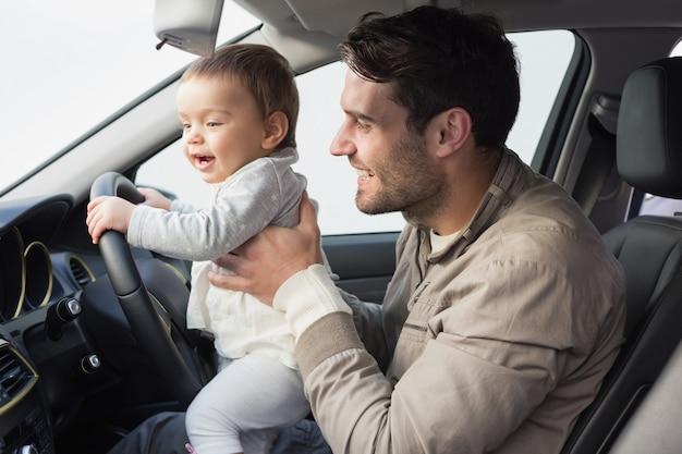 Père jouant avec bébé dans le siège du conducteur
