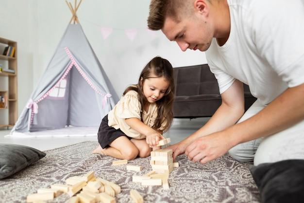 Père jouant avec sa fille à la maison