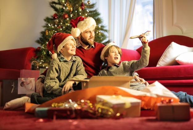 Père jouant avec ses fils, tout en ouvrant les cadeaux de noël