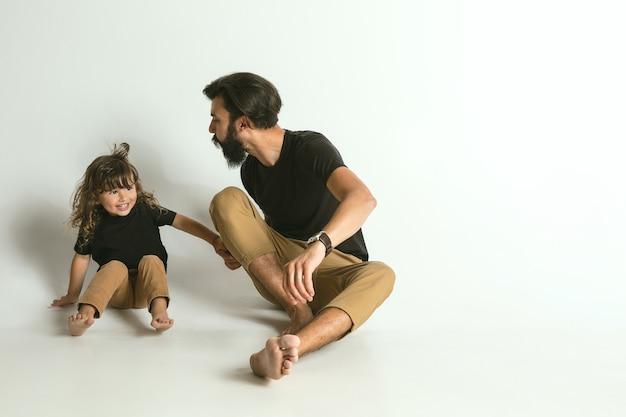 Père jouant avec son jeune fils contre blanc