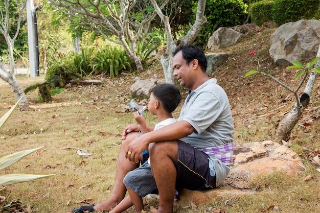 Père joue au savon à bulles avec son fils dans le parc