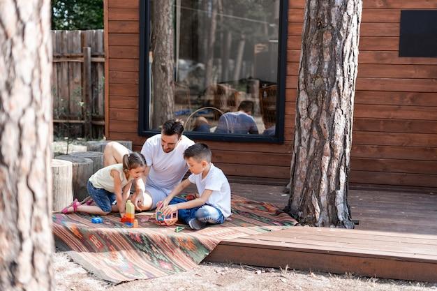 Un père joue avec deux enfants assis sur le porche près d'une maison de campagne en bois, passe son temps libre à aider les enfants à jouer avec des jouets, passe des vacances avec sa famille