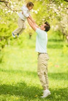 Père joue avec la jolie petite fille dans le parc de l'été.