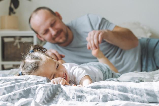 Le père joue avec la petite fille 2-4 sur le lit. papa chatouille les pieds des enfants. famille, s'amuser