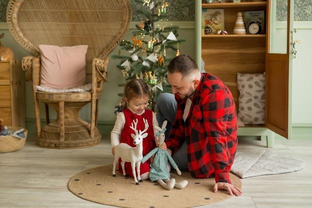 Un père joue avec sa fille dans une chambre d'enfant avec un sapin de noël
