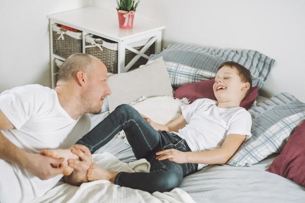 Père joue avec son fils 7-10 au lit. papa chatouille les pieds des enfants. famille, s'amuser
