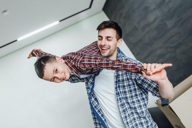 Un père joue avec son fils dans une nouvelle maison moderne des émotions joyeuses le week-end du déménagement