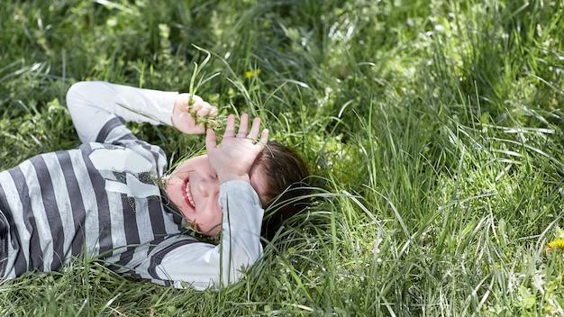 Père joue avec son petit-fils sur l'herbe dans le parc.