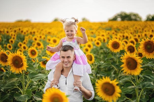 Père joue et tourne avec sa fille dans le champ de tournesol.